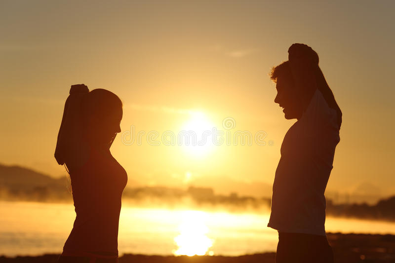 Silhouette of a fitness couple stretching at sunrise royalty free stock images
