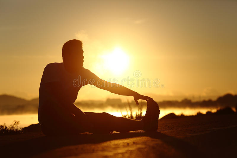 Silhouette of a fitness man stretching at sunset. Silhouette of a fitness runner man stretching at sunset with the sun in the background royalty free stock photo