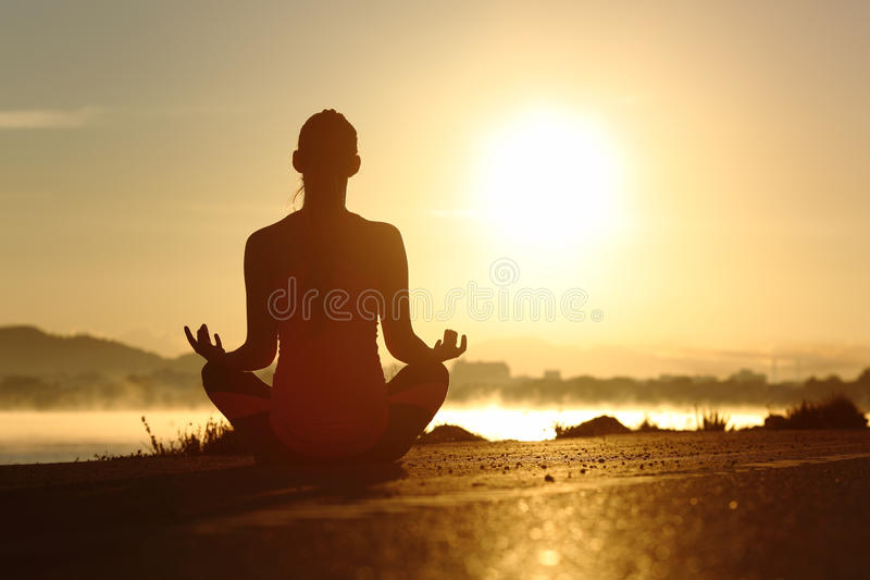 Silhouette of a fitness woman exercising yoga meditation exercises stock photography