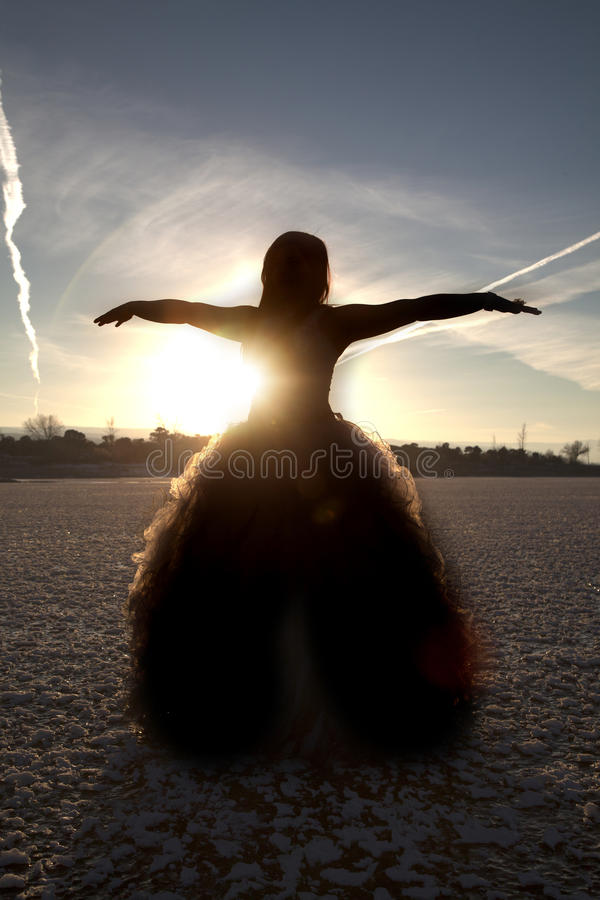 Silhouette formal ice arms out. A silhouette of a woman with her arms out in her formal dress on a frozen lake royalty free stock photos