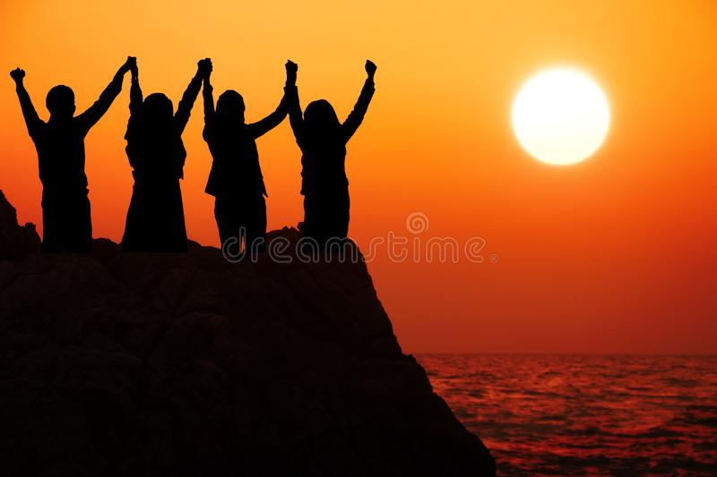 Silhouette four business people make high hands when business success ,teamwork concept. stock image