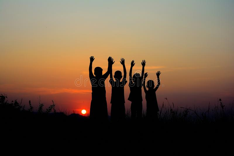 silhouette of four children standing together. There is a sky at sunset background royalty free stock photography