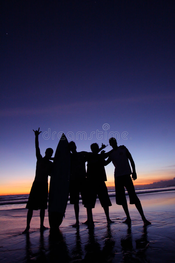 Silhouette of four men holding a surfboard on the beach royalty free stock image