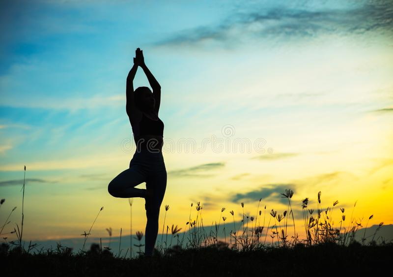 Silhouette of woman praying over beautiful sky background. Silhouette of free cheering woman hiker open arms at mountain peak beautiful sky background stock image