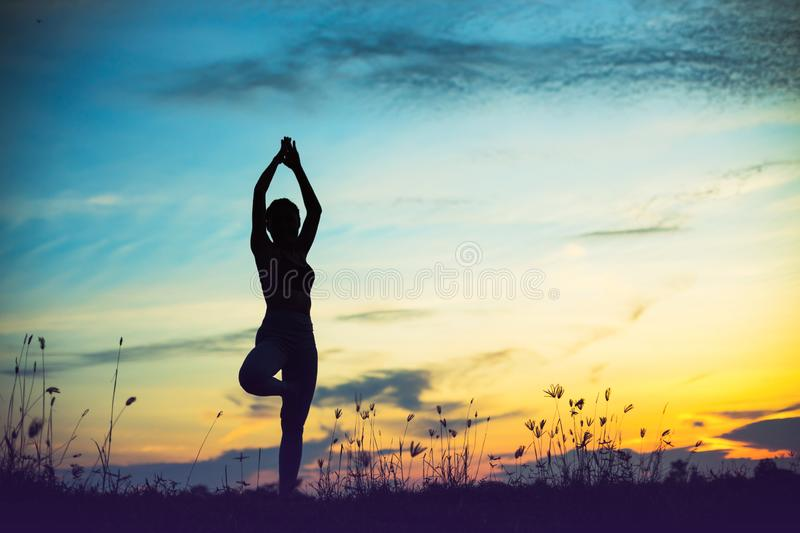 Silhouette of woman praying over beautiful sky background. Silhouette of free cheering woman hiker open arms at mountain peak beautiful sky background stock photo