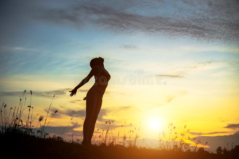 Silhouette of woman praying over beautiful sky background. Silhouette of free cheering woman hiker open arms at mountain peak beautiful sky background stock photos