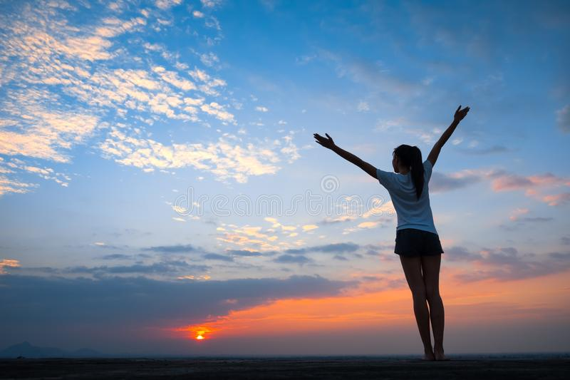Silhouette of woman freedom feeling in sunset. Silhouette of free woman enjoying freedom feeling happy at sunset. Serene relaxing woman in pure happiness stock image