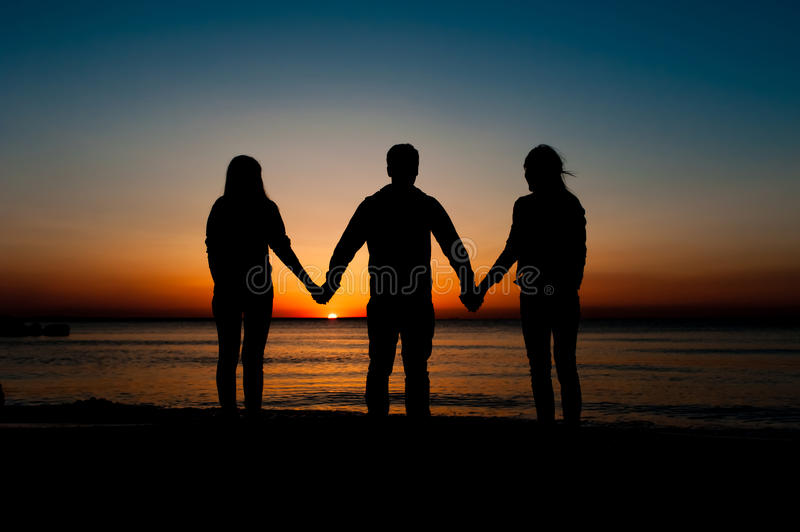 Silhouette of friends on beach stock image