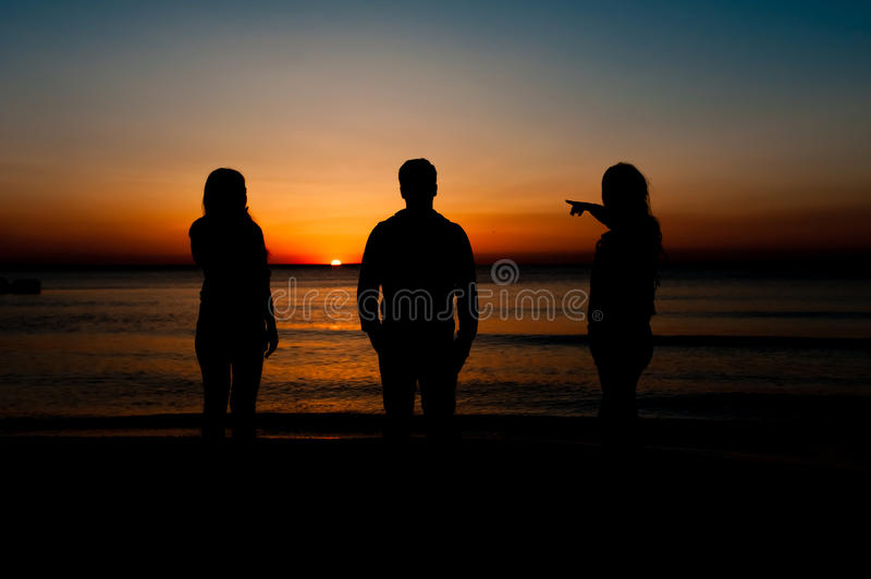 Silhouette of friends on beach stock photo