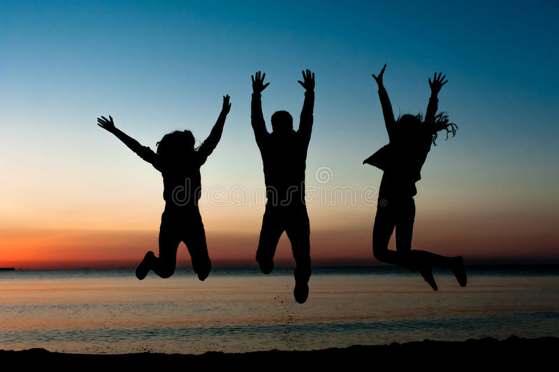 Silhouette of friends jumping on beach royalty free stock photos