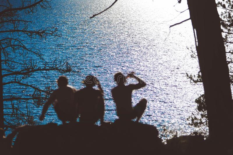 Silhouette of friends sitting on a rock  near the beautiful Lake Tahoe, CA reflecting the sunlight stock photo