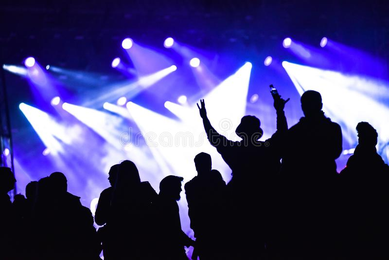 Silhouette of friends socializing at a festival. Cheerful crowd partying at a concert. Silhouette of friends socializing at a festival. Stage lights in the stock photography
