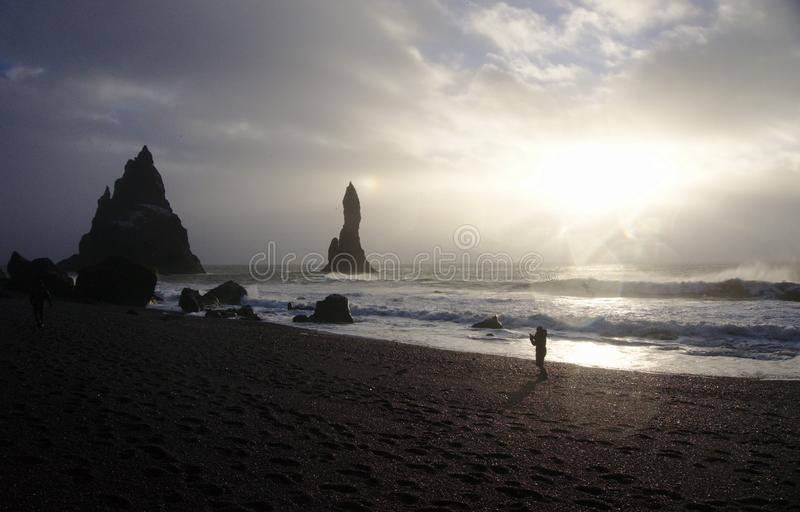 Silhouette in front of waves on the shore of black sand beach, Iceland stock photo
