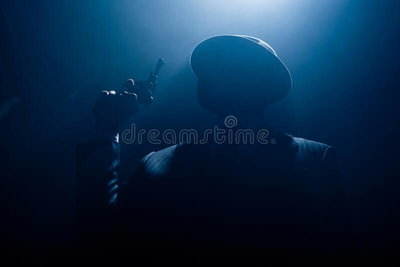 Silhouette of gangster in suit and. Felt hat with revolver on dark background stock image