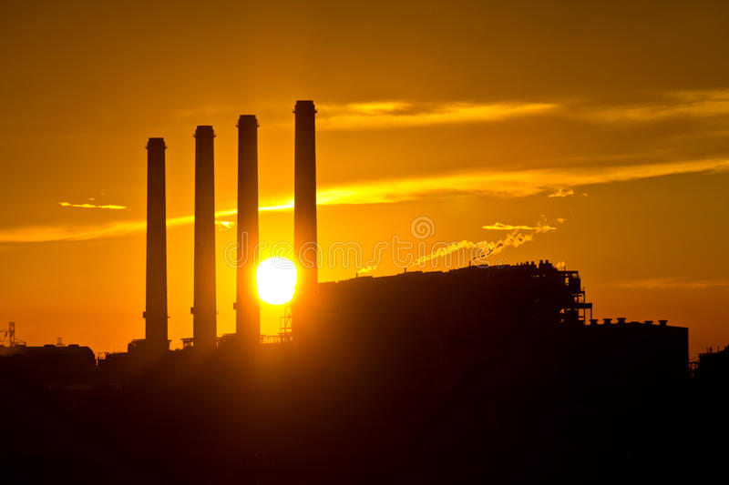Silhouette of gas turbine electrical power plant. Against sunset royalty free stock images