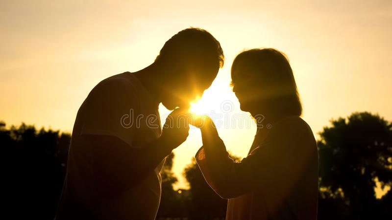 Silhouette of gentleman kissing wife's hand, senior couple in love, romance stock photo