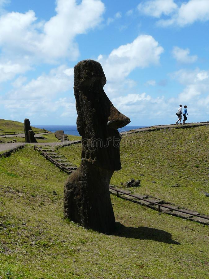 Silhouette of a giant statue of Moai, Rano Raraku, Easter Island. Silhouette of a giant monolithic statue of Moai sticking out of the ground on the slopes of an royalty free stock image