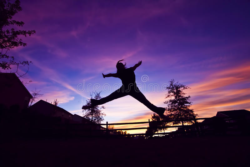 Silhouette of a girl. A girl does a star jump into the air against a purple sky stock photo