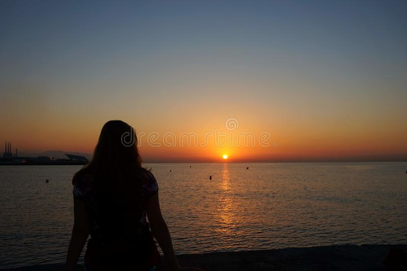 Silhouette of a girl against the background of the rising sun on the Balearic Sea. royalty free stock images