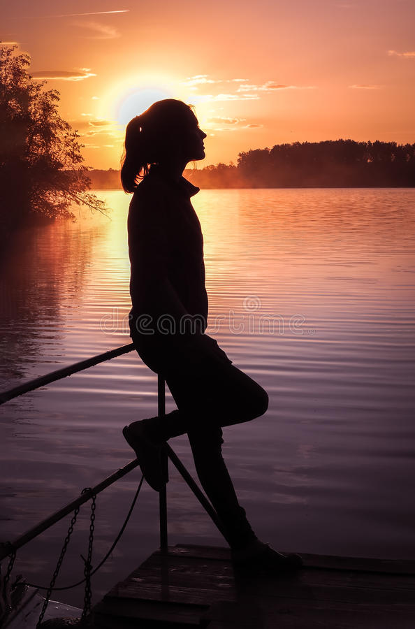 Silhouette girl background sun. Girl standing near water outdoors. Gold sunset lake. Young woman thinking about something river du. Silhouette of a girl on the royalty free stock photo