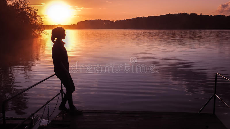 Silhouette girl background sun. Girl standing near water outdoors. Gold sunset lake. Young woman thinking about something river du. Silhouette of a girl on the royalty free stock photos
