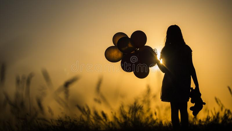 Silhouette of a girl with balloons and a teddy bear. It is worth the sunset. Farewell to childhood concept royalty free stock photo