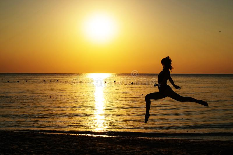 Silhouette of a girl in a bathing suit running along the beach on the background of the dawn.  royalty free stock image
