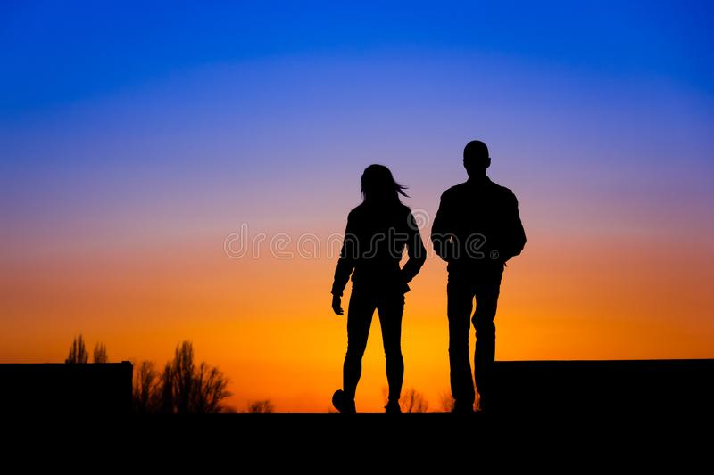 The silhouette of a girl and a boy at sunset royalty free stock images