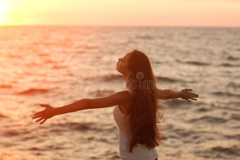Silhouette of a girl doing yoga and mediation at sunset by the sea. stock images