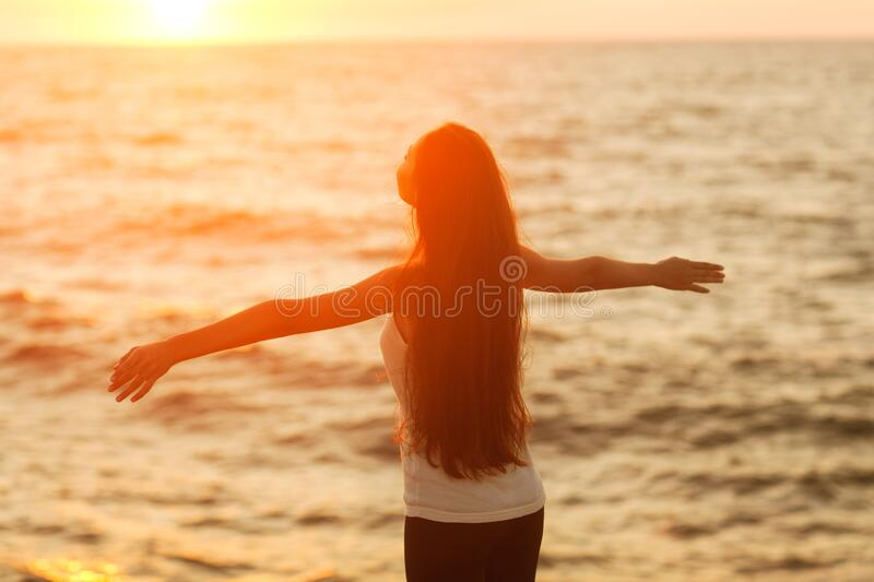 Silhouette of a girl doing yoga and mediation at sunset by the sea. royalty free stock photo