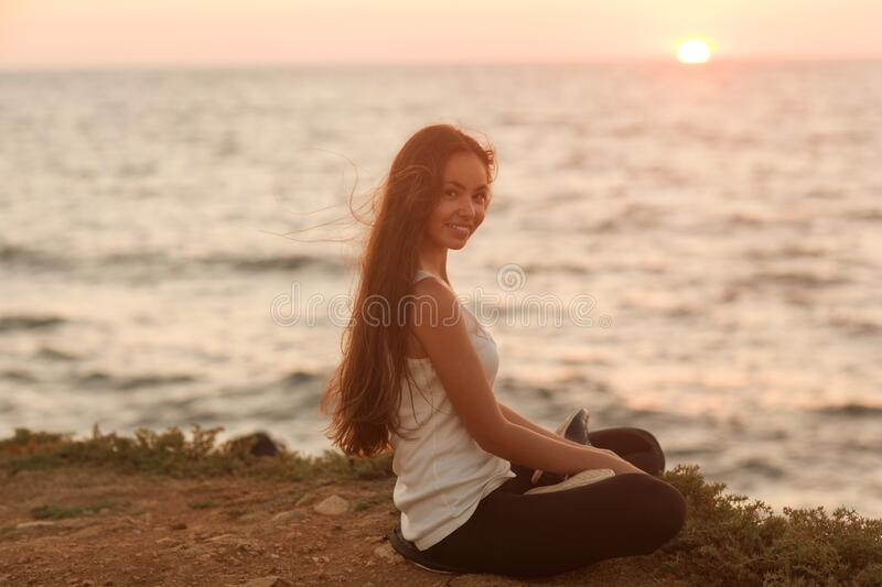 Silhouette of a girl doing yoga and mediation at sunset by the sea royalty free stock photo