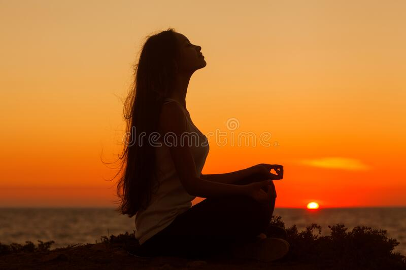 Silhouette of a girl doing yoga and mediation at sunset by the sea stock image
