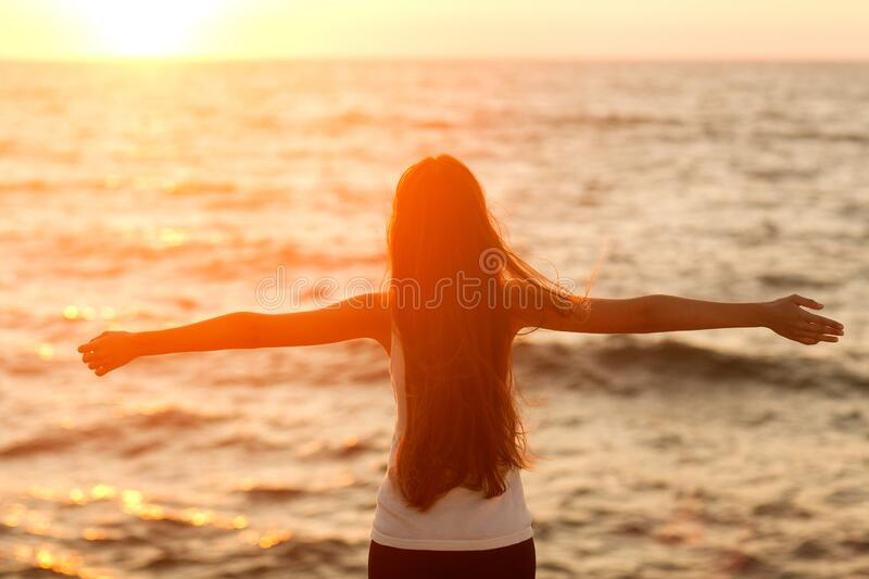 Silhouette of a girl doing yoga and mediation at sunset by the sea. stock photo