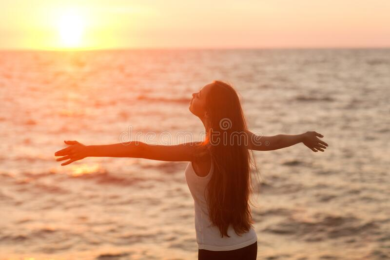 Silhouette of a girl doing yoga and mediation at sunset by the sea. stock photos