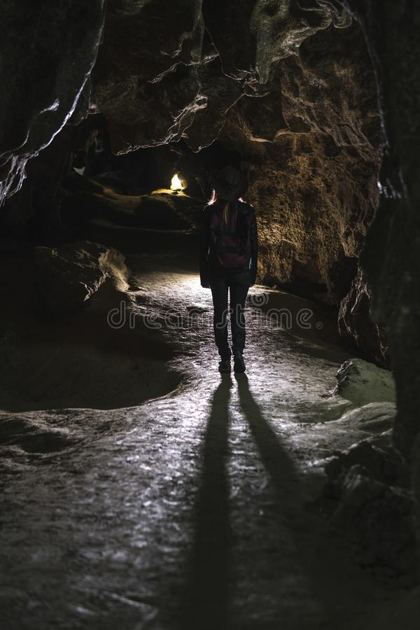 Silhouette girl exploring huge cave. Adventure traveller dressed cowboy hat and backpack, leather jacket. Vertical photo, tourist royalty free stock images