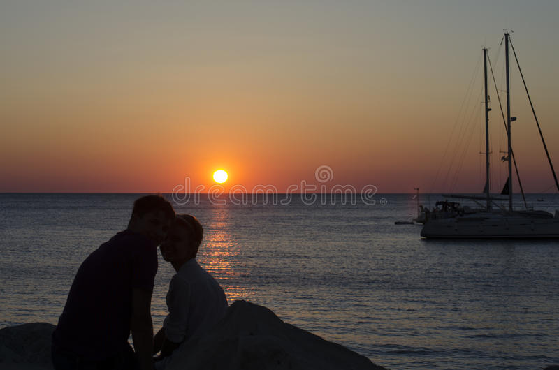 Silhouette of the girl and guy looking at the sunset stock photography