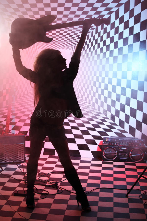Silhouette of girl holding electric guitar overhead in studio. In smoke and pink and blue light stock photo