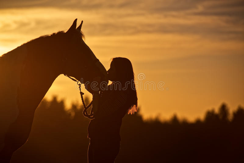Silhouette of Girl Kissing Horse. A young woman with long hair is seen kissing her horse as the golden sun sets in the background stock photography