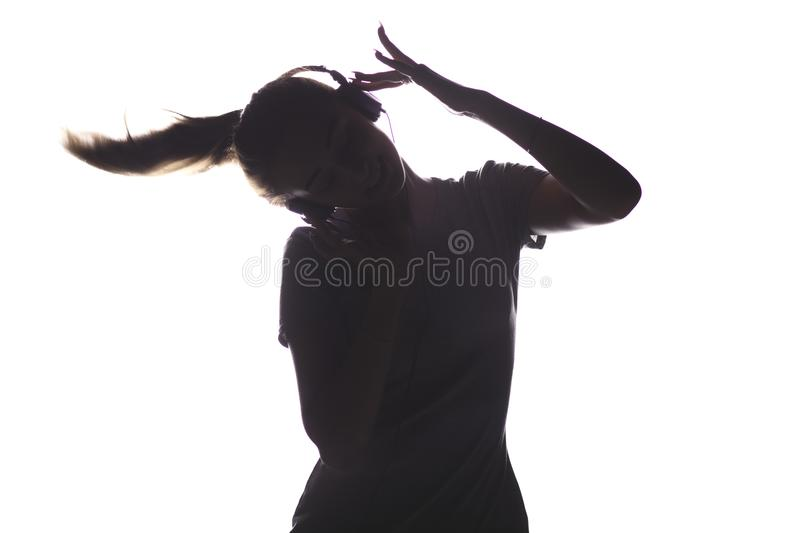 Silhouette of a girl listening to music in headphones, young woman relaxing on a white isolated background, concept of hobby and l stock photo