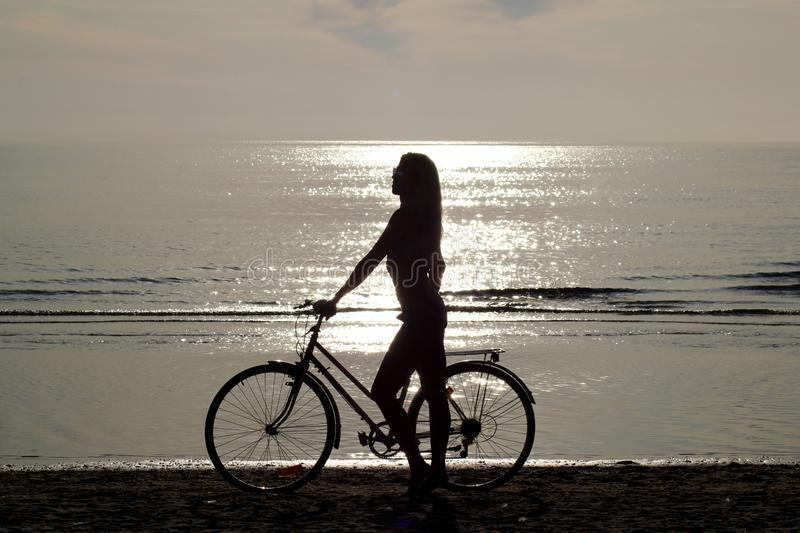Silhouette of a girl with long hair on a bicycle riding on the sand by the Baltic sea. Shooting against the sun royalty free stock photos
