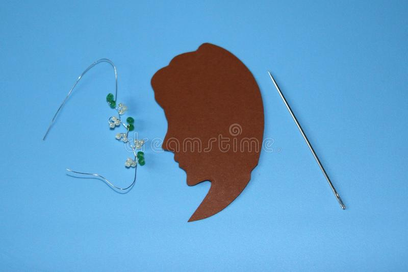 Silhouette of a girl made of brown paper and a needle, jewelry made of small green and white round beads and a thin metal wire stock photography