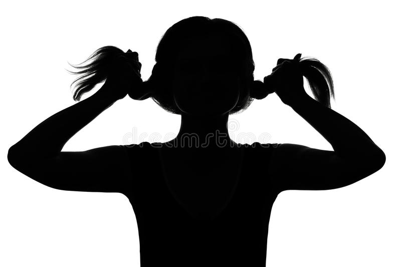 Silhouette of a girl playing with pigtails stock photo