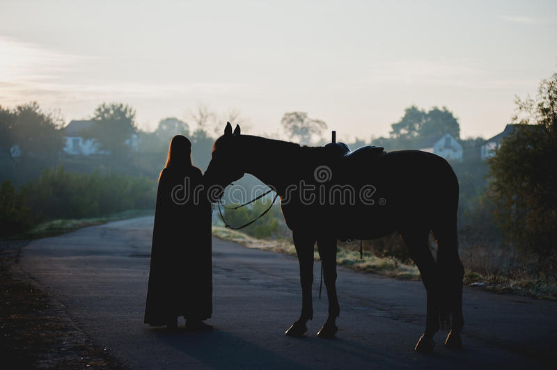 Silhouette of a girl in a raincoat kissing a horse on dark background with blue mist royalty free stock photography