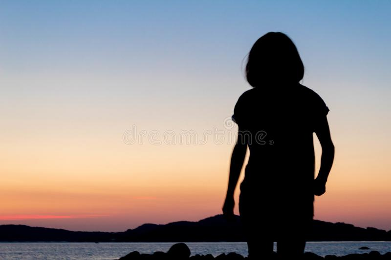 Silhouette of a girl on the beach royalty free stock image