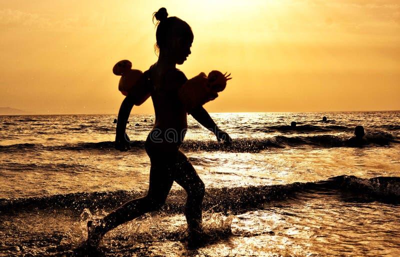 Silhouette of Girl Running on the Seashore during Golden Hour stock photo
