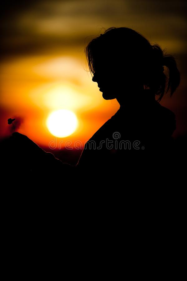 Silhouette of girl`s face holding cloverleaf during sunset - Black and orange colors. Silhouette of girl`s face holding cloverleaf during sunset time - Black and royalty free stock photo
