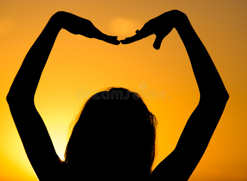 Silhouette of a girl's hand on a beautiful sunset royalty free stock images
