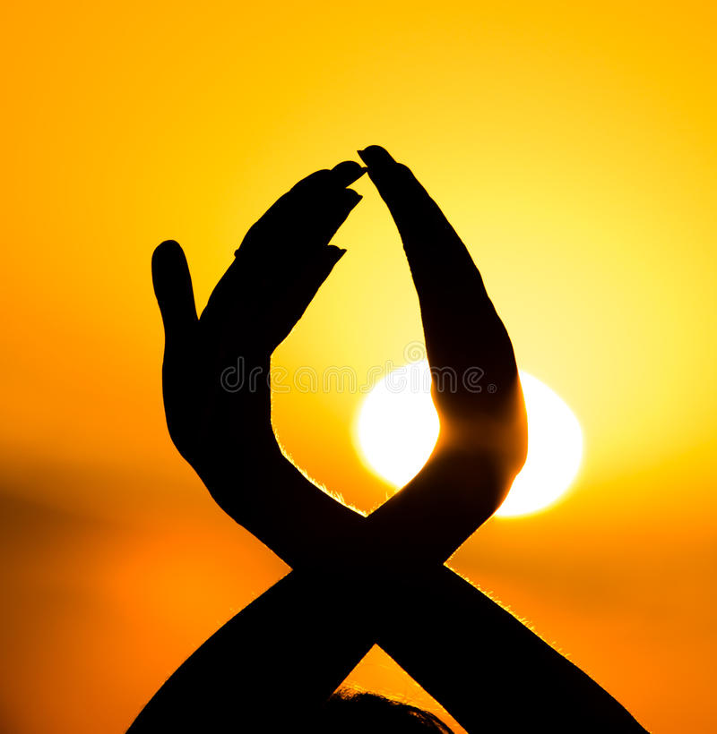Silhouette of a girl`s hand on a beautiful sunset royalty free stock photo