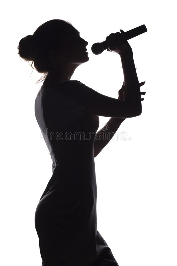Silhouette of girl singing into microphone, profile of young woman face performing lyric song on white isolated background. Silhouette of beautiful girl with stock photos
