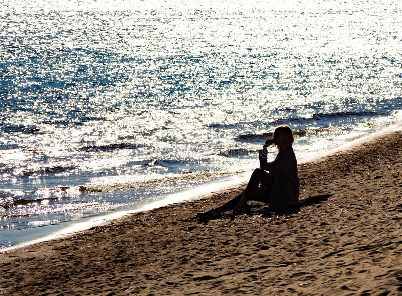 Silhouette of a girl sitting on the shore. Silhouette of a girl sitting on the shore with a sparkling water royalty free stock image
